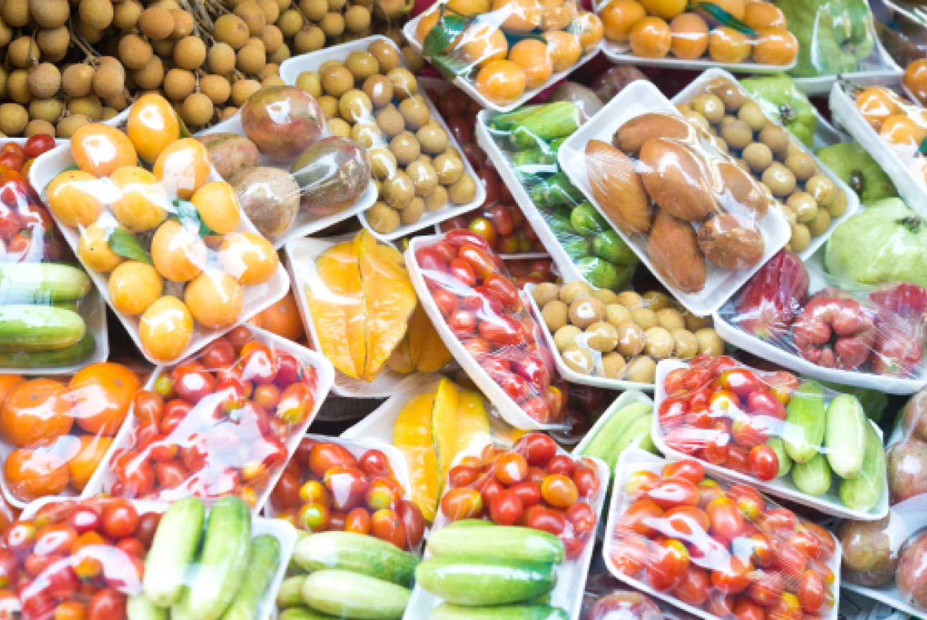 Plastic-wrapped fruits and vegetables at a grocery store.