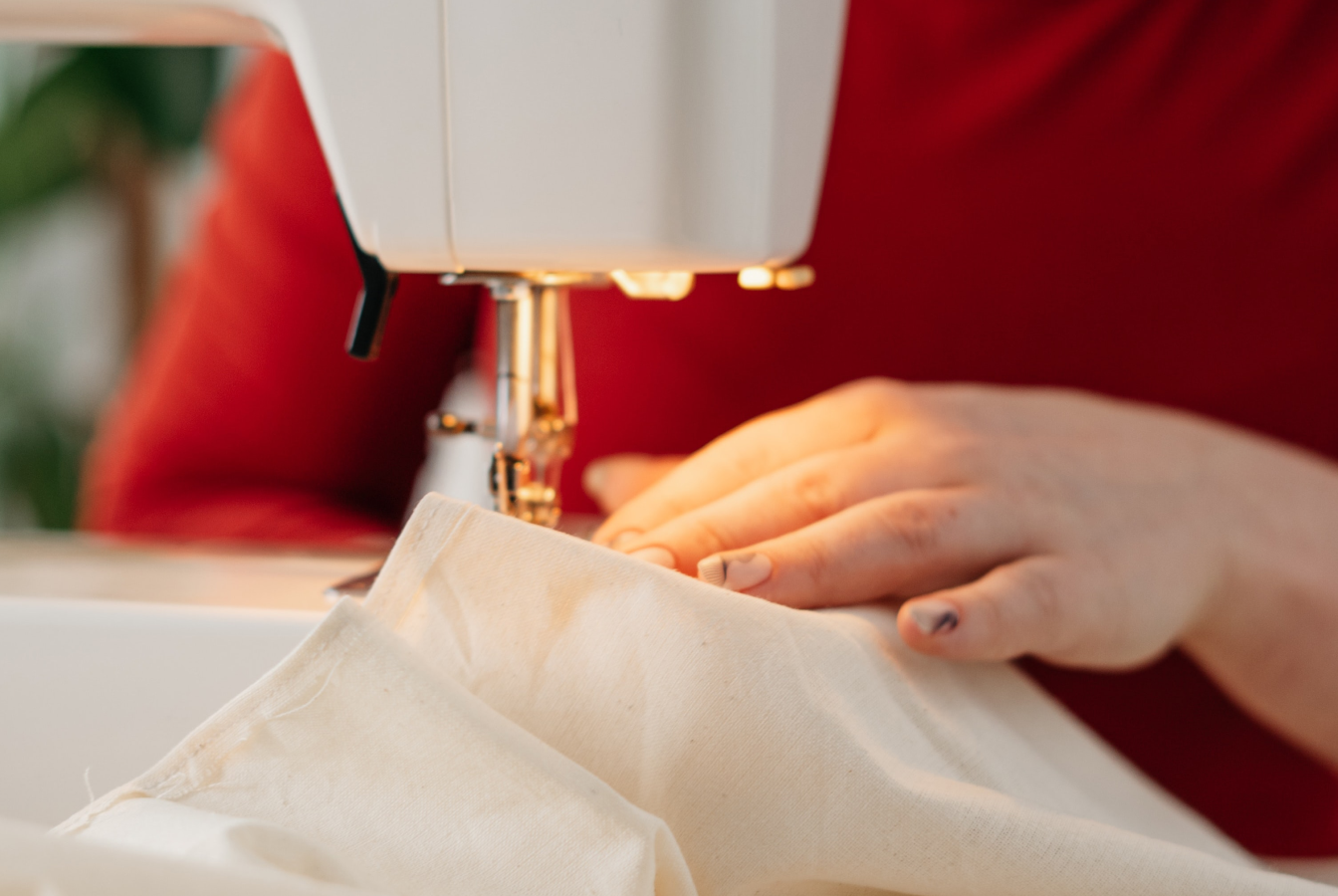 A person sewing an sustainable dress to give as a gift.
