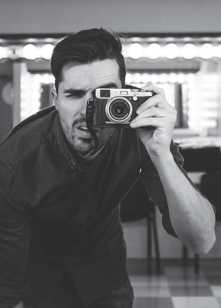 A picture of a guy looking through a camera