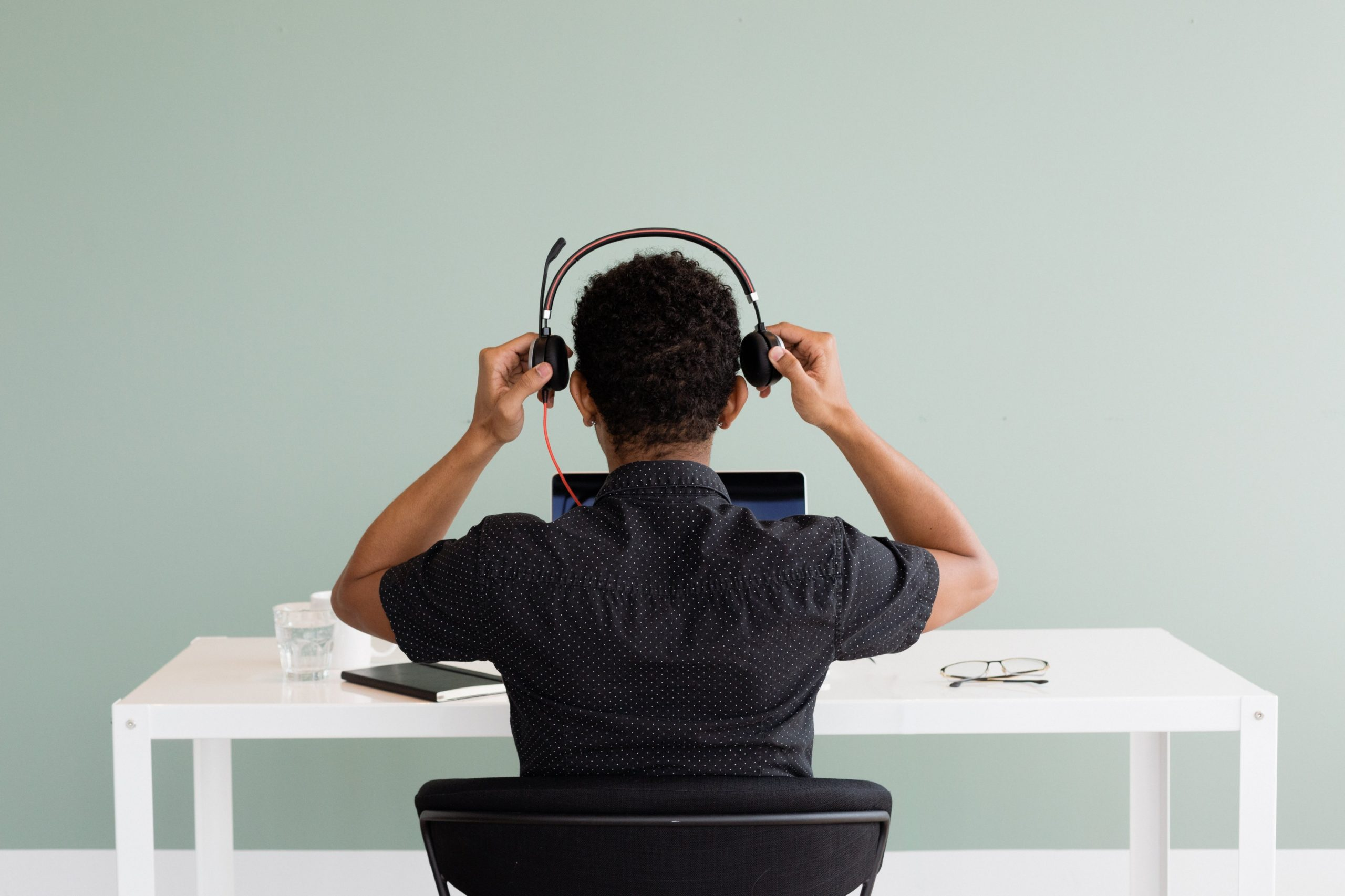 person with headset sitting at a desk
