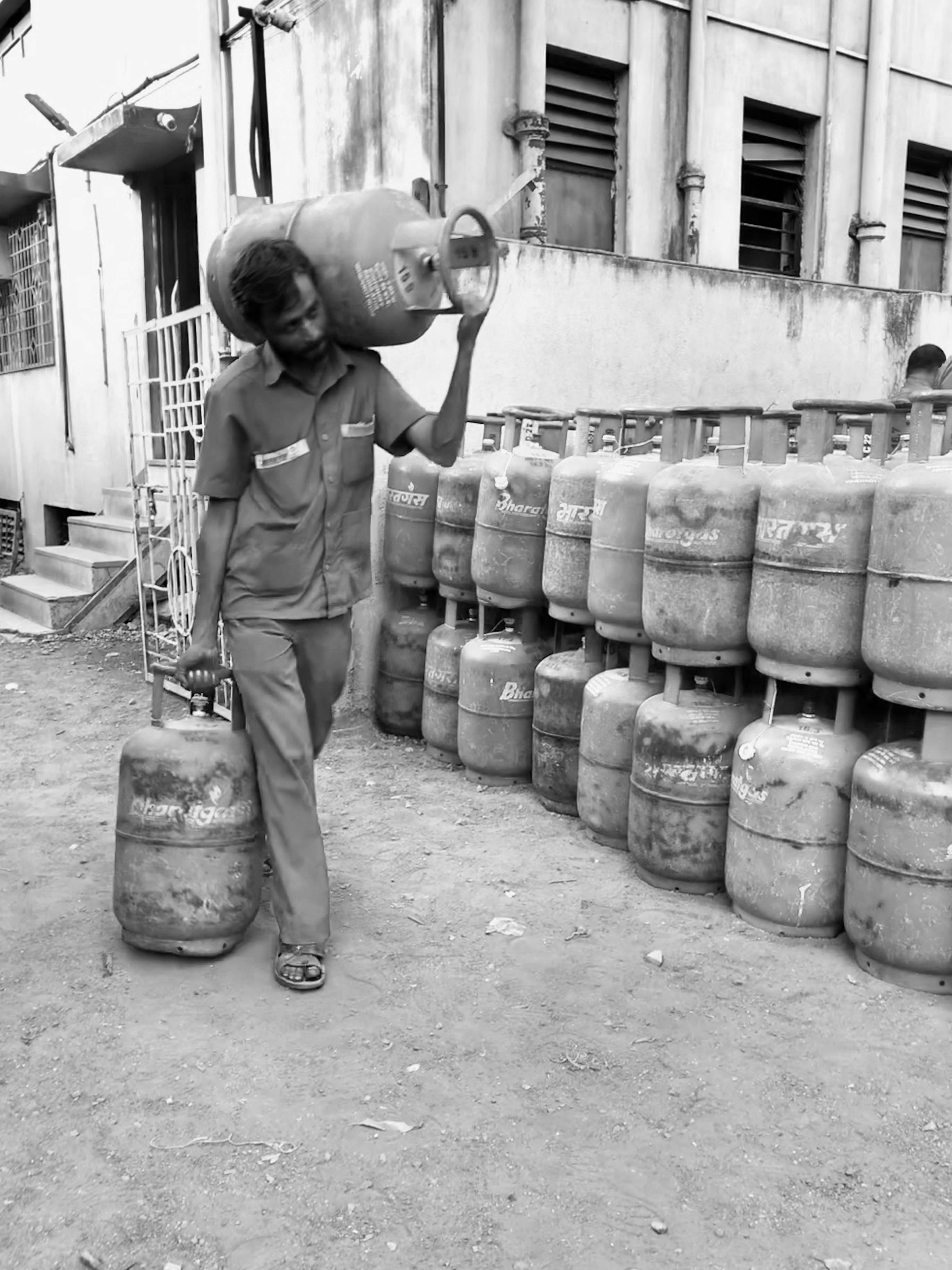 A delivery guy carrying two heavy cylinders with LPG.
