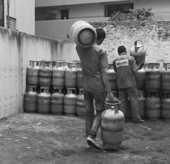 two men carrying and stacking cylinders
