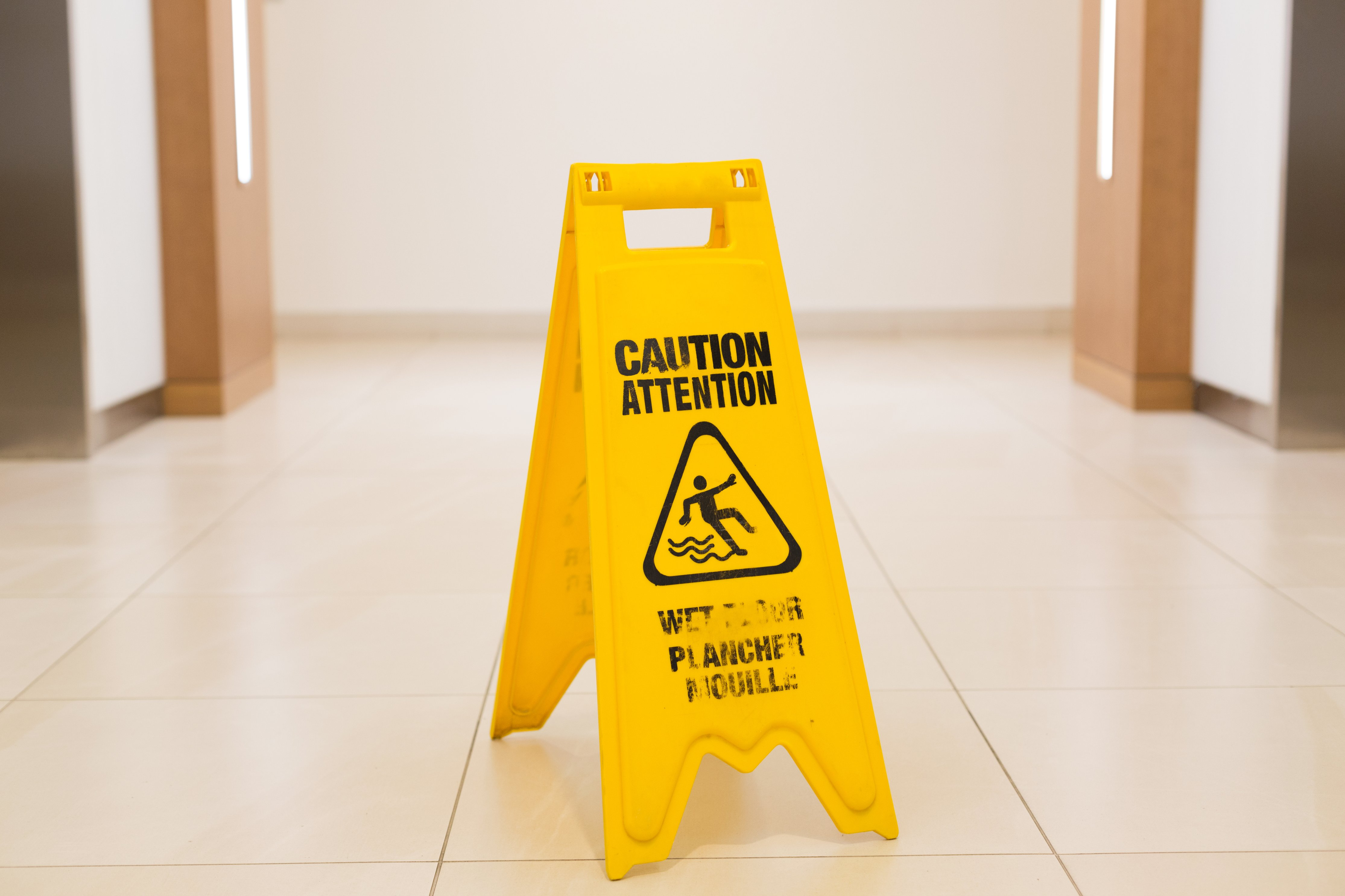 photo of a sign that warns about the wet floor and danger of slipping
