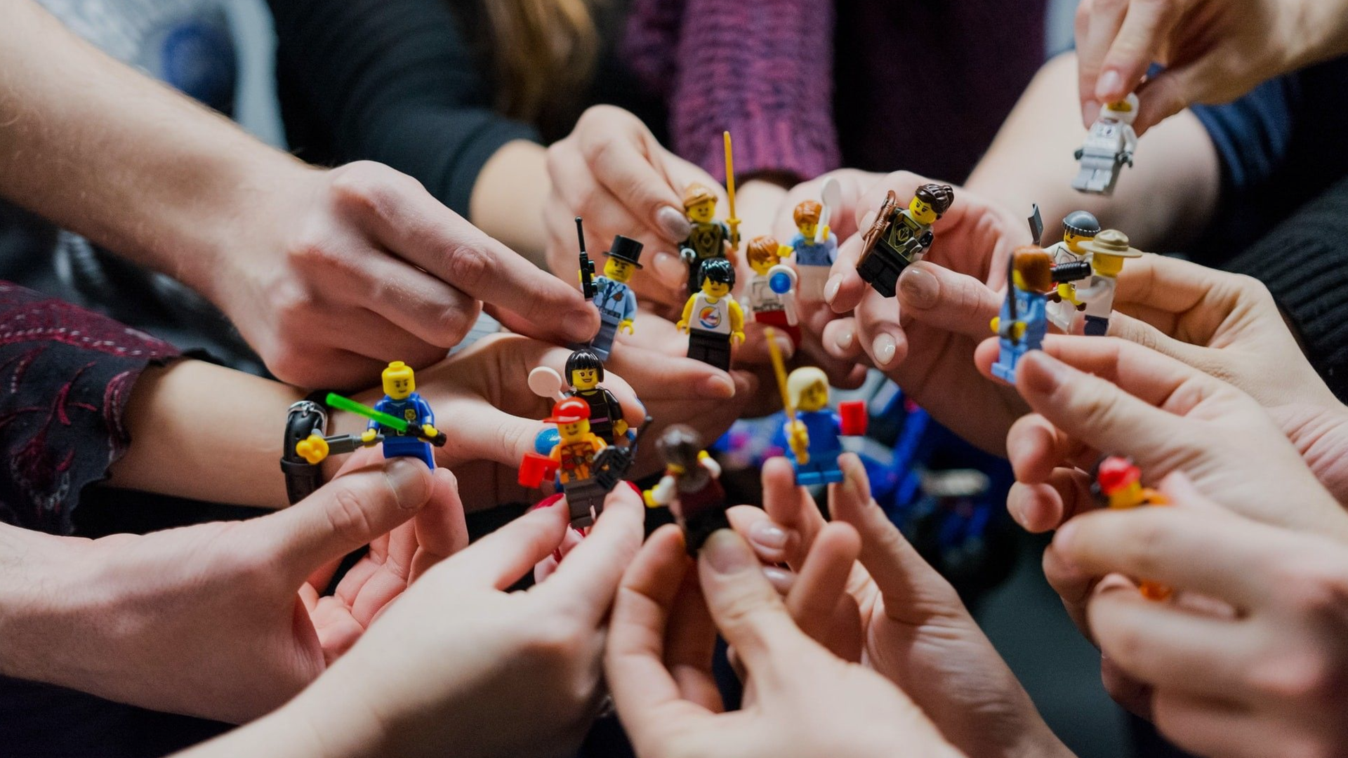 many hands, each holding a lego play figure