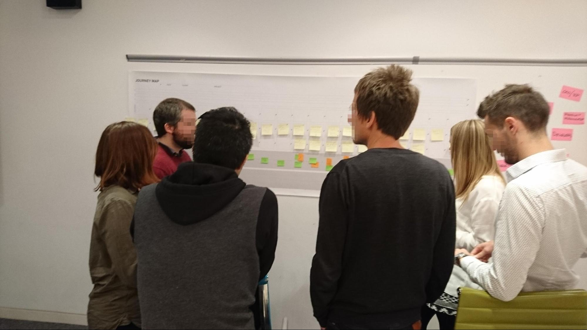 A group of people standing around a pen-and-paper journey template, discussing and creating the storyboard.