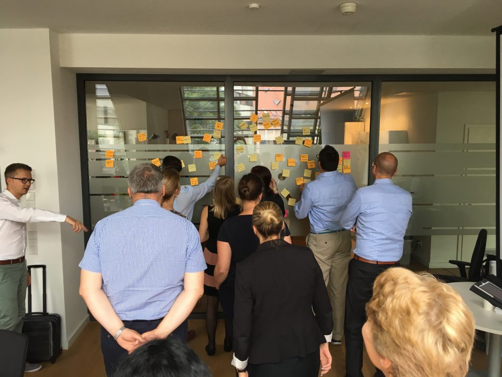 people standing in front of a glasswall clustering sticky notes