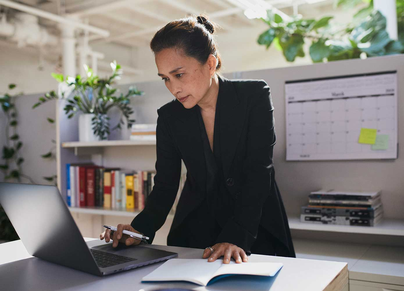 Woman standing and looking into a laptop