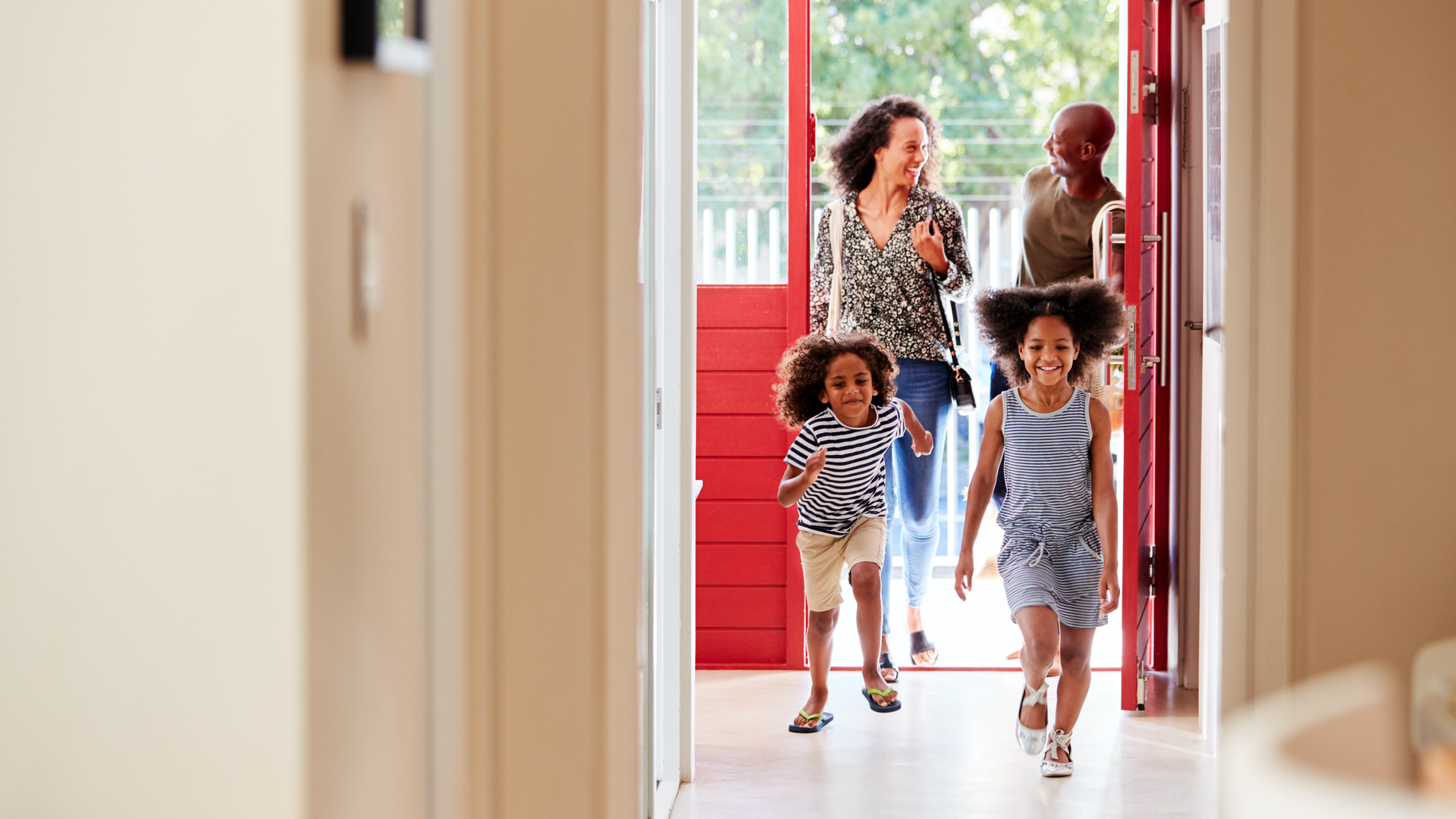 Family entering home with children excitedly running.