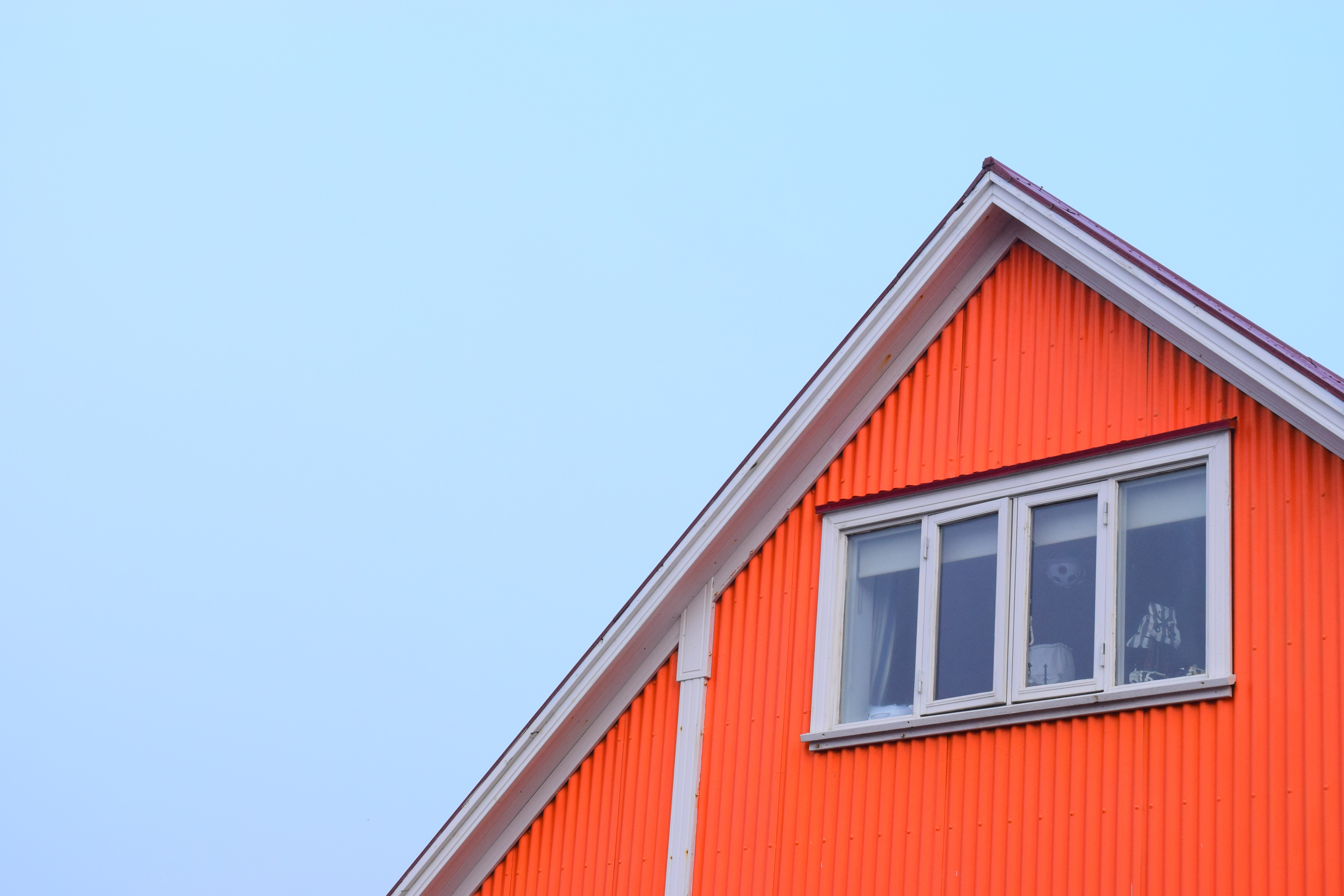 Roof of home with bright orange siding against blue sky.