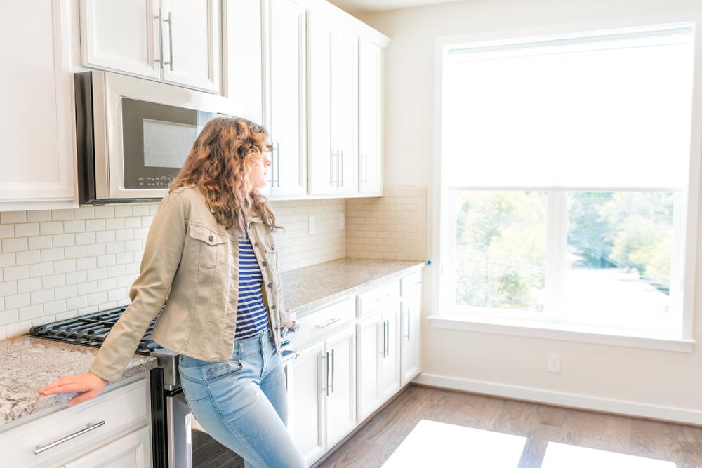 Young woman standing in bright, modern kitchen.