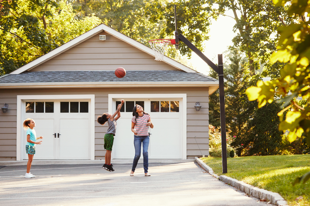 Family playing basketball in driveway.