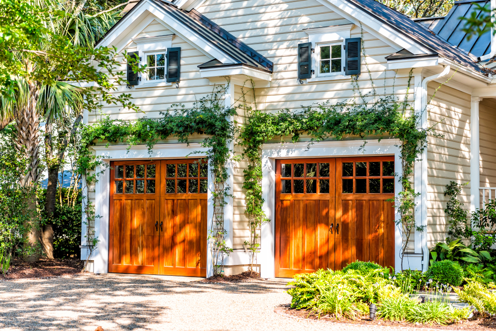 Charming garage with ivy and wood doors.