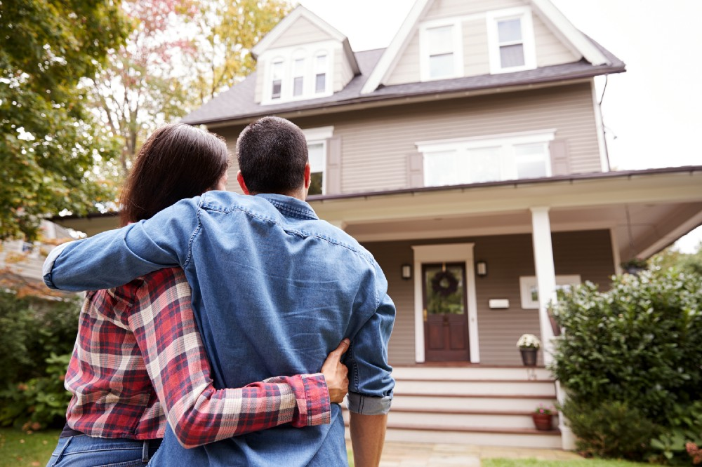 Couple embraces and looks at their home from the front yard