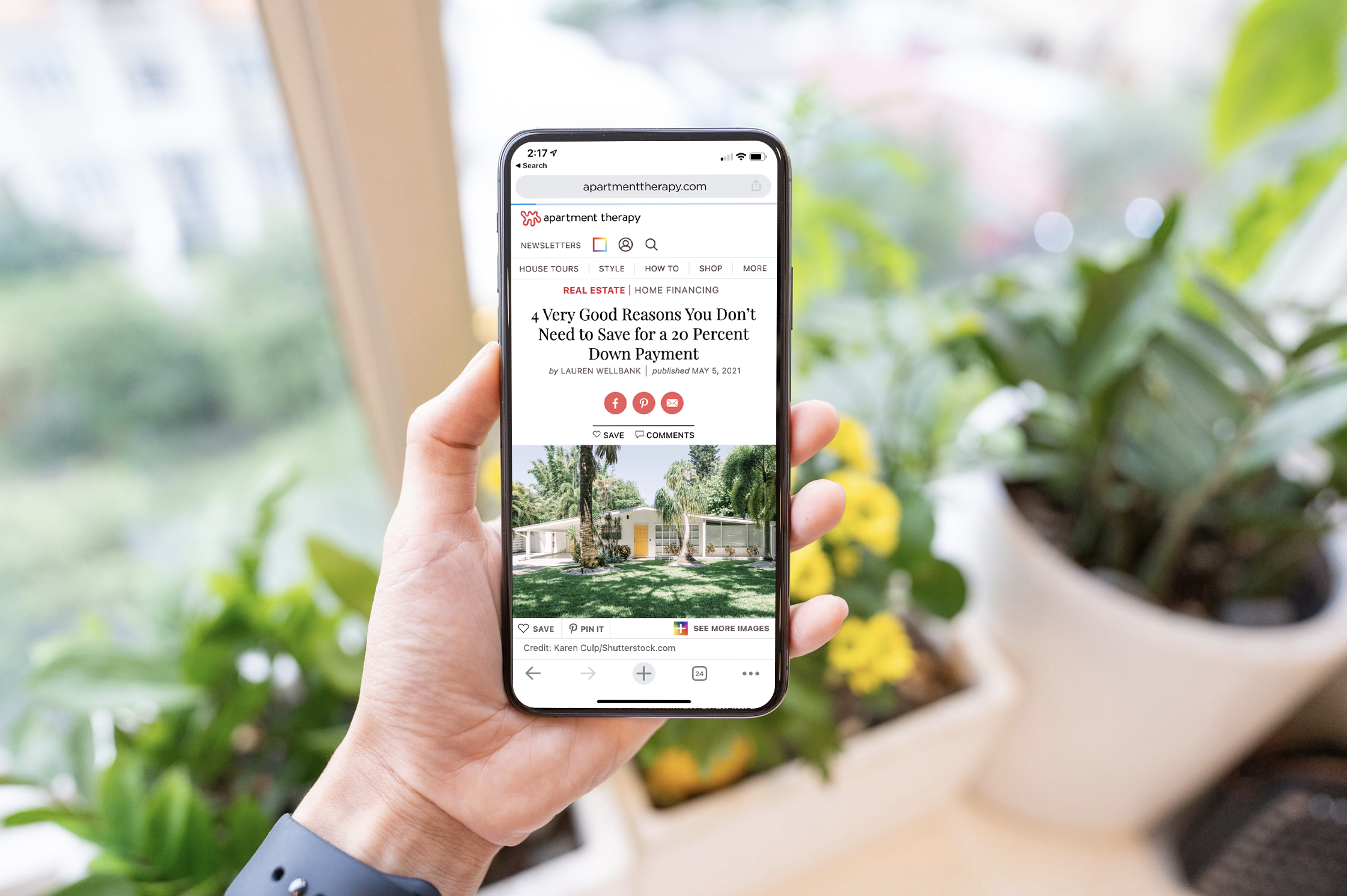 Hand holding iPhone showcasing Apartment Therapy article