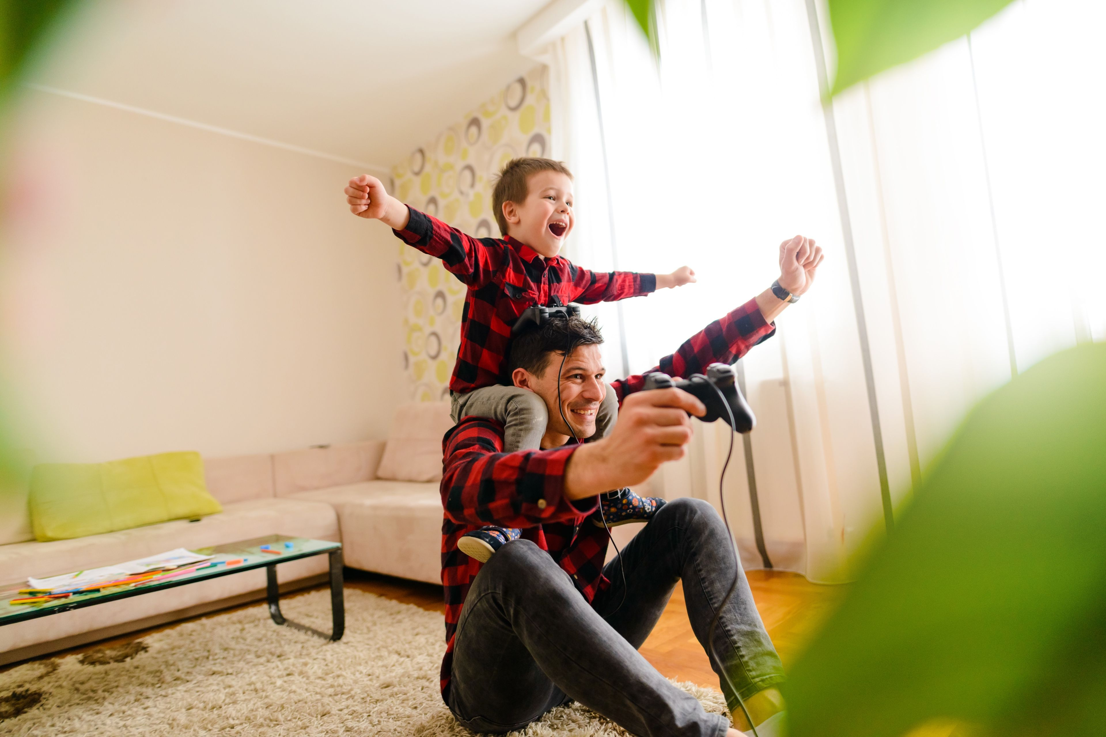 Dad playing games with son. How to Pick the Right Mortgage Lender for Your Refinance 5 Things Besides Interest Rate to Consider
