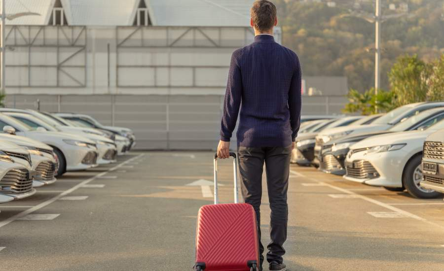 Man with suitcase looking at cars wondering how to get the best deal on a rental car