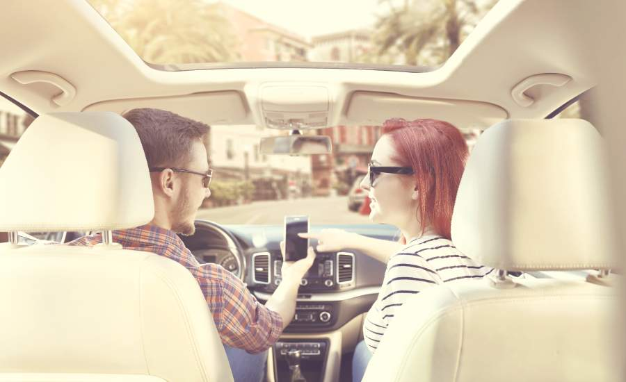 couple in front seat of car talking