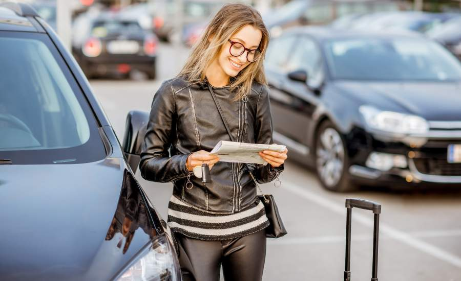 woman checking her phone next to car