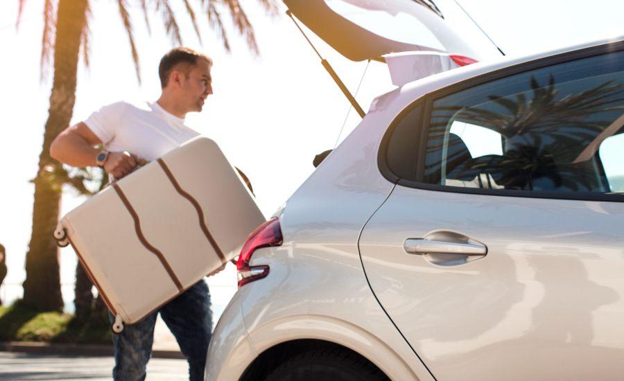 man putting luggage in car