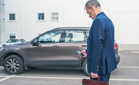 man checking his phone in the parking lot