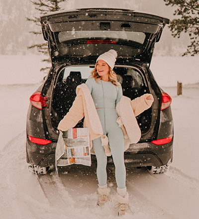 girl laughing in snow outside car