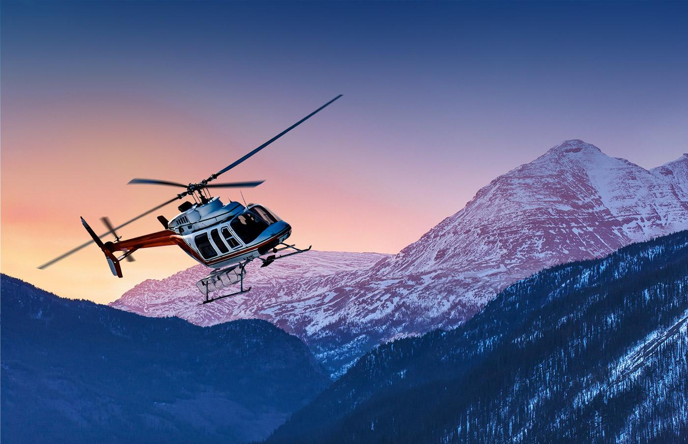 Helicopter flying over a Yukon mountain range at sunrise desktop version.