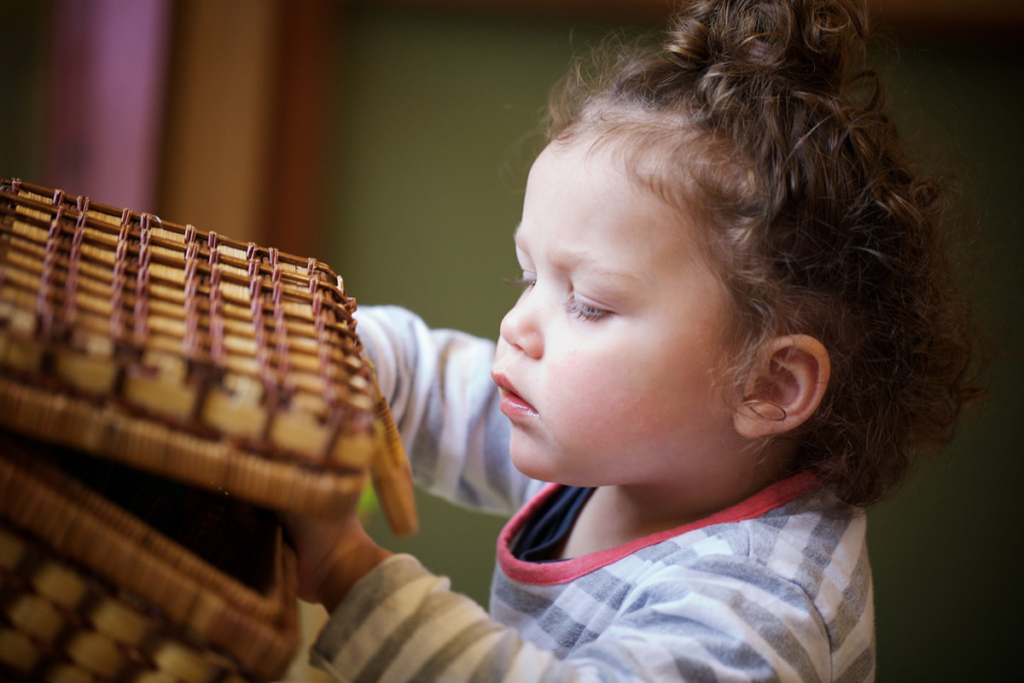 Toddler looking into a wooden basket