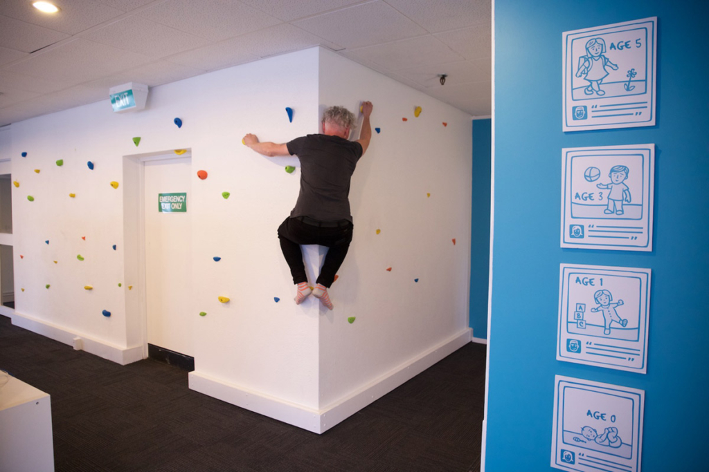 Man climbing to a wall indoors