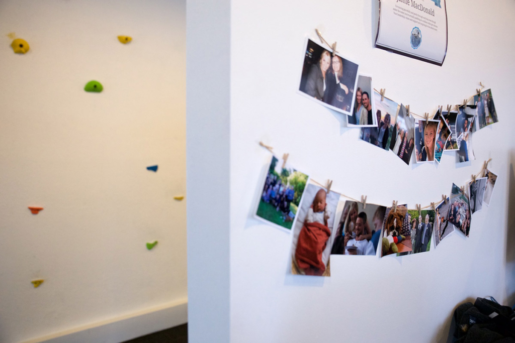 photos of people and children hang onto a wall