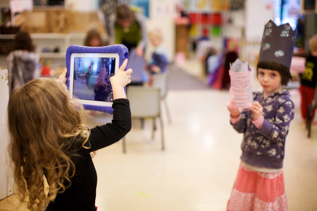 Toddler taking a photo of her friend with an ipad