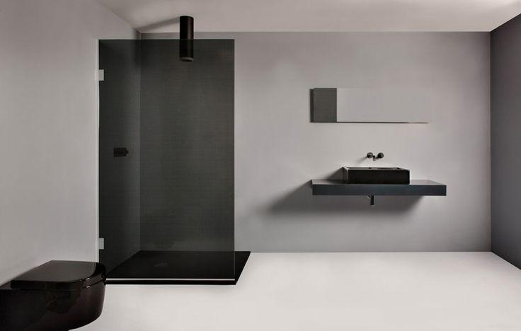Een zwarte douchewand in combinatie met beton