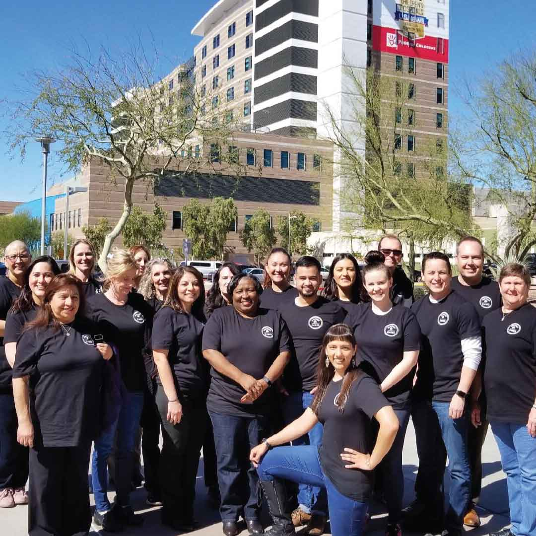 SunWest staff wearing SunWest Cares t-shirts huddle for a group photo outside Phoenix Children's Hospital on a sunny day