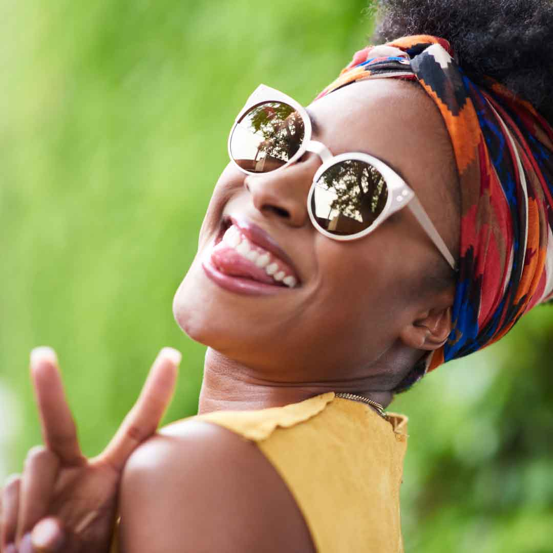 "a smiling young woman wearing a colorful headband looks over her should and signals the ""peace"" sign with her middle and index fingers"