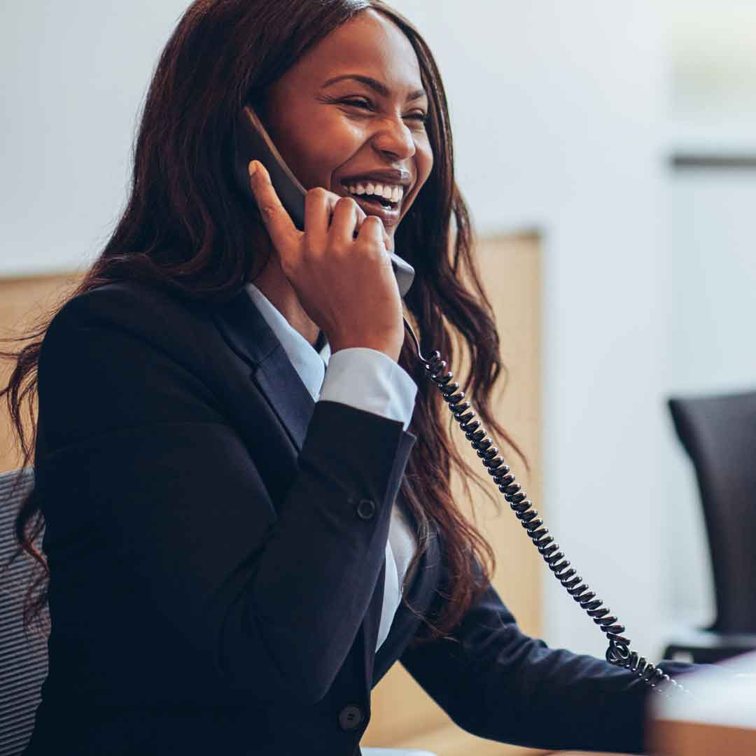 a business woman smiles while talking on the phone in the office