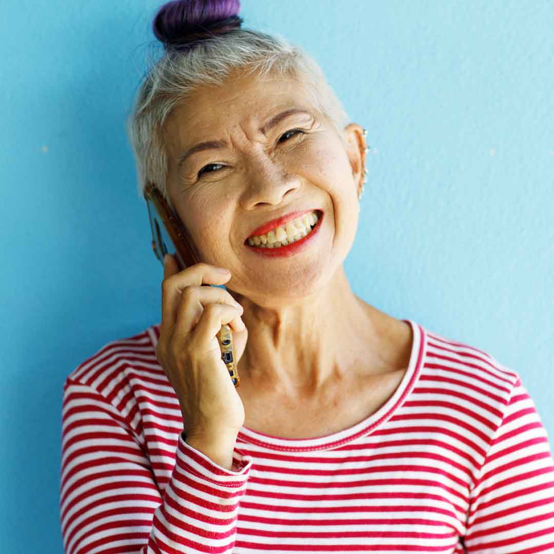 a stylish senior woman smiles while chatting on her smart phone