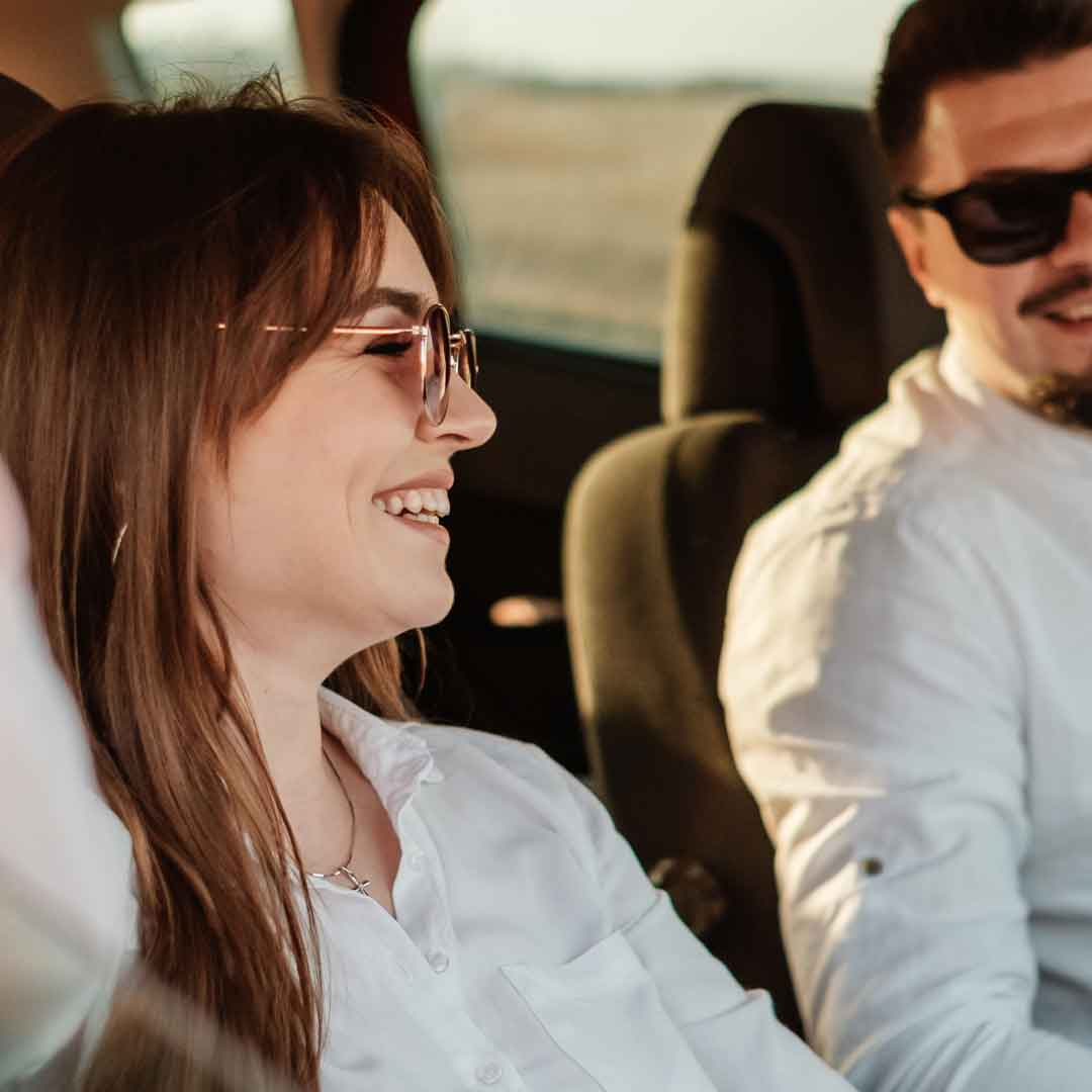 a young couple laugh together while driving through the country in their car