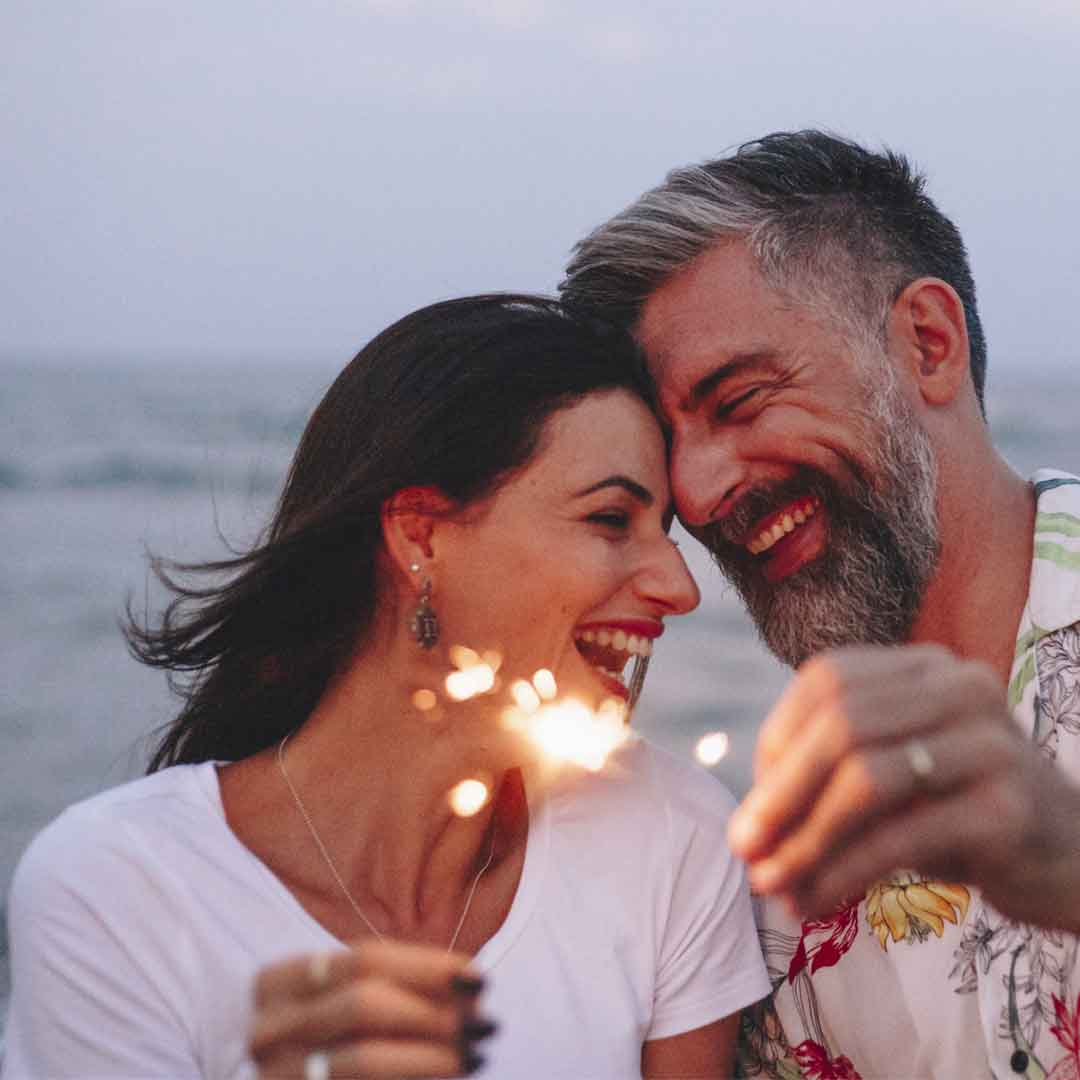 a mature couple lean their smiling faces together while holding sparklers on the beach at twilight