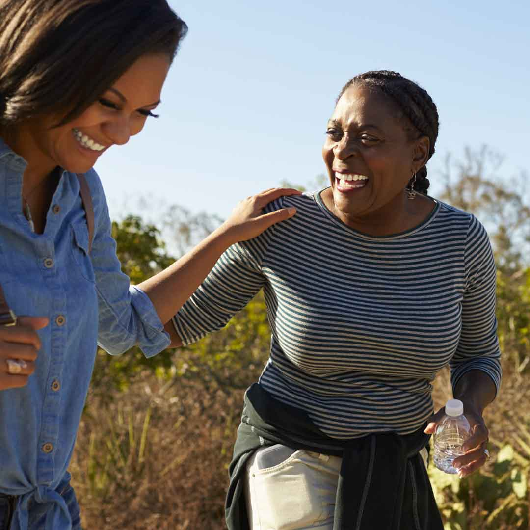 an adult daughter grabs her mother's shoulder in an outburst of laughter as they hike along a trail