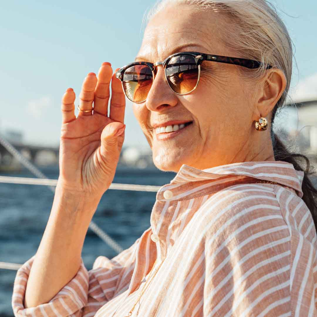 a posh, mature woman adjusts her stylish sunglasses as she looks out at sea from a sailboat