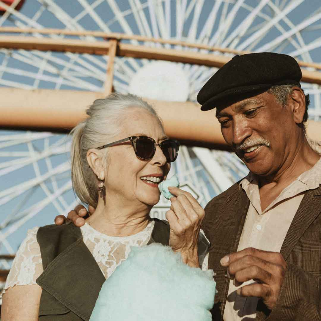 a mature couple share cotton candy on a sunny day at the amusement park with a ferris wheel in the background