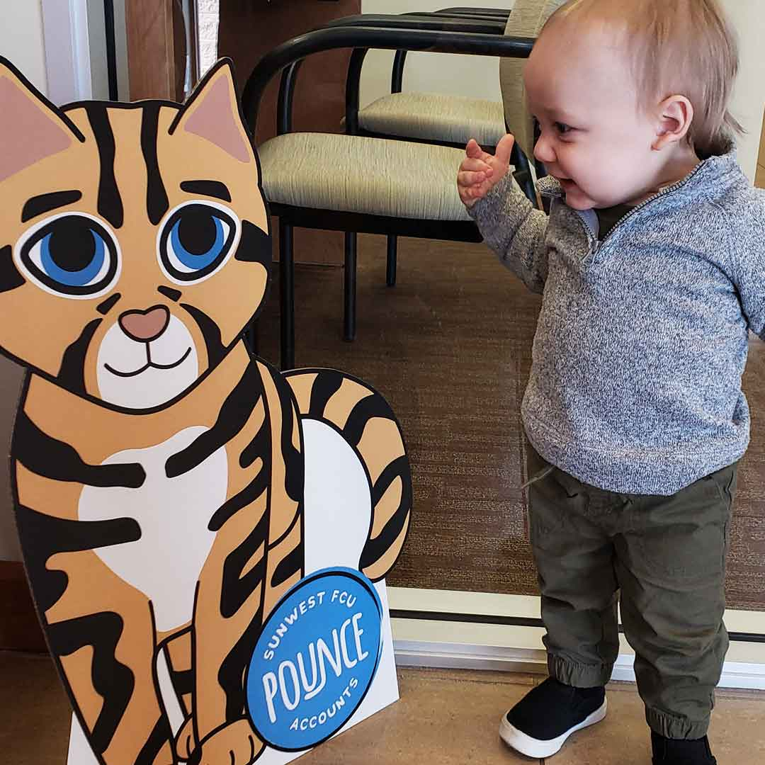 Toddler boy smiles with delight as he makes eye contact with Pounce's cardboard cutout in a SunWest branch