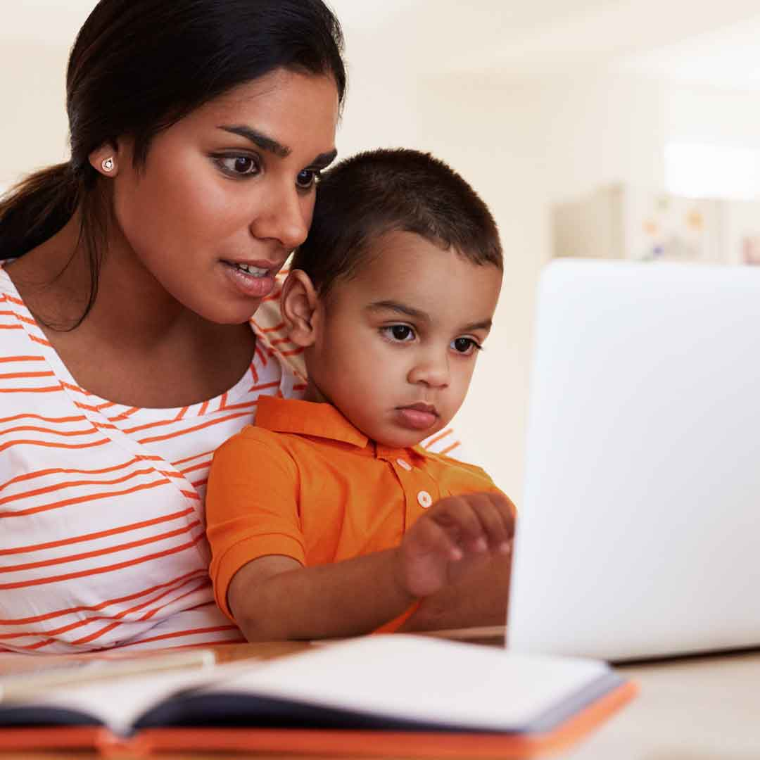 a mother holds her son on her lap as they sit at a table with an open book and laptop