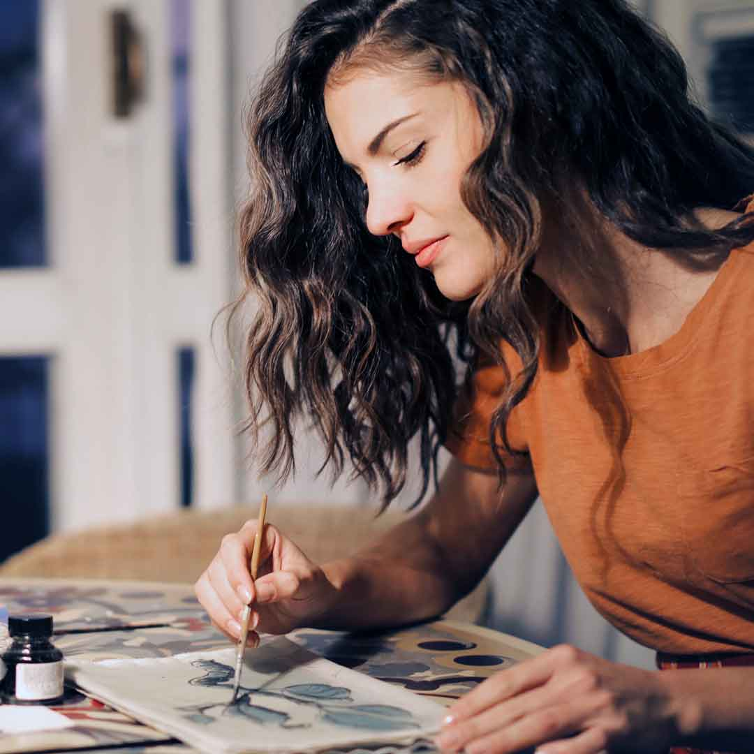 a teenage girl paints with watercolors at the kitchen table