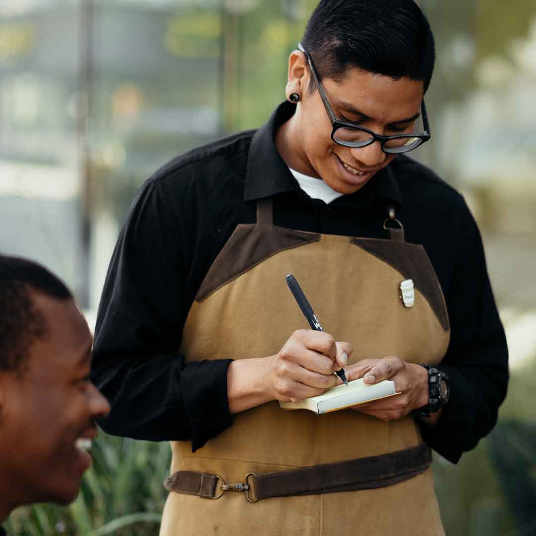 a male teen server writes down a customer's order at an outdoor cafe