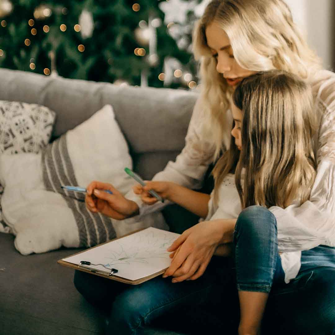 a young mother and daughter color coloring sheets on a comfy couch by a Christmas tree