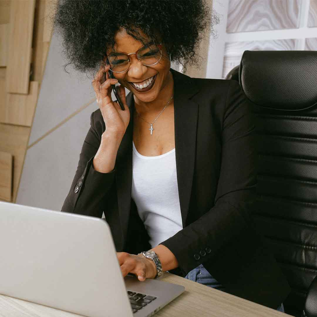 a business woman wearing a black blazer laughs while talking on the phone and typing on her open laptop at her desk