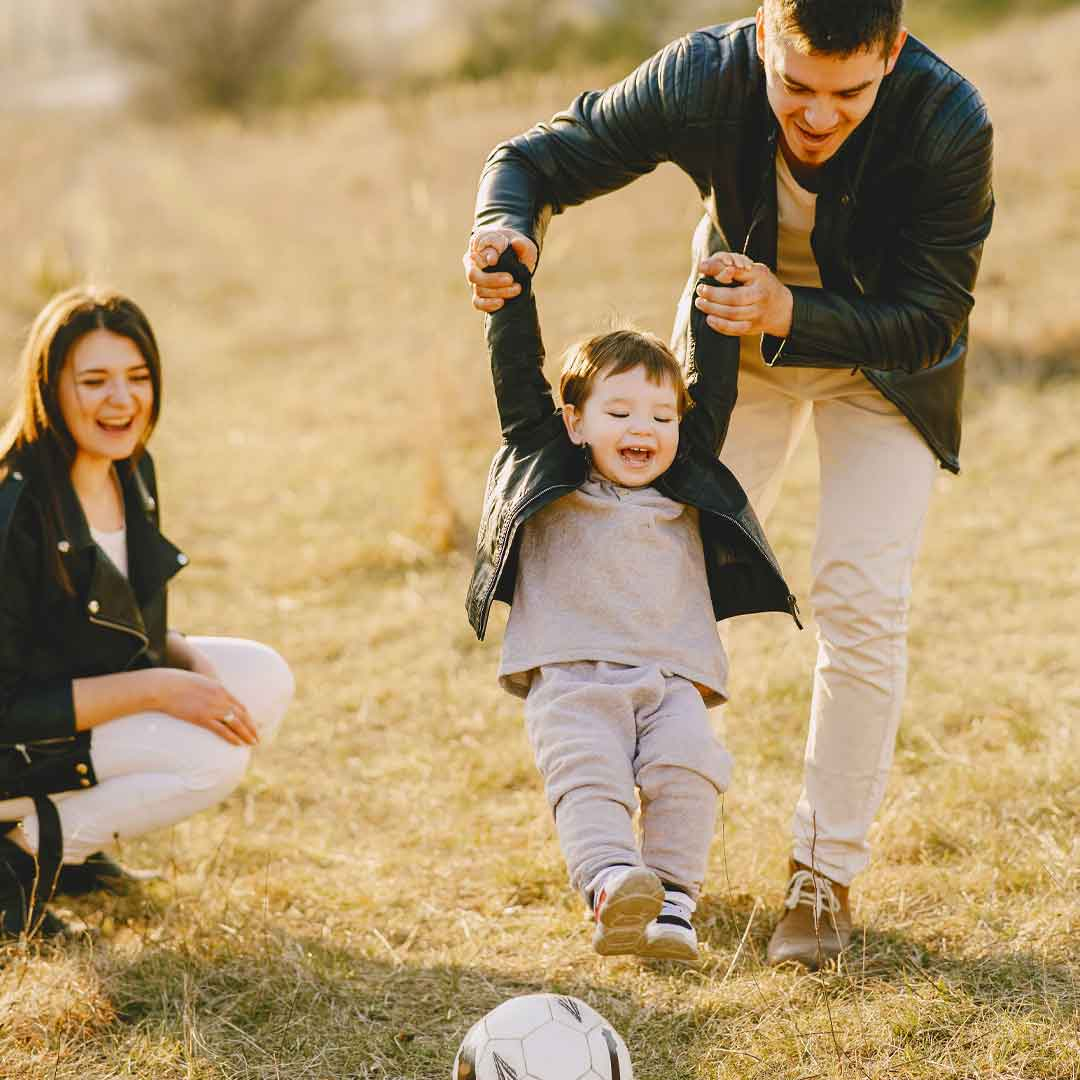 a father holds his toddler son's hands while he kicks a soccer ball with joy