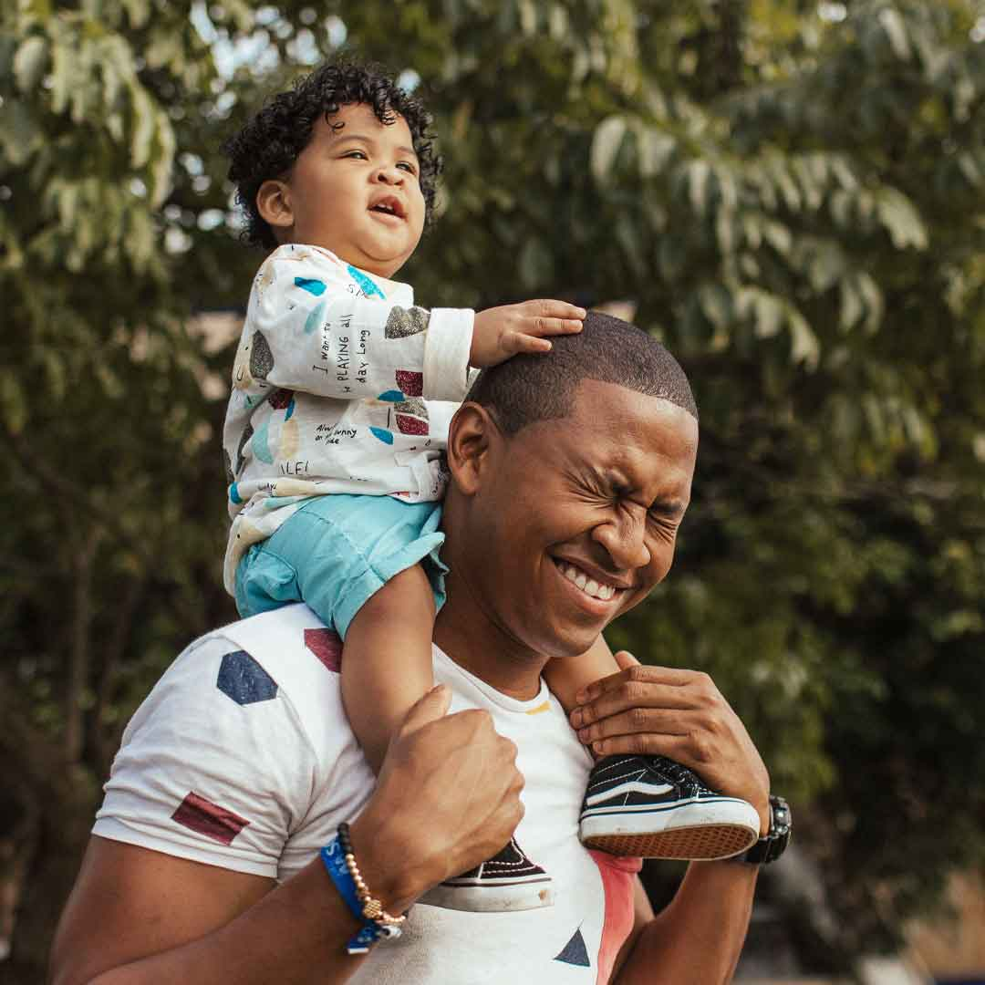 a father laughs while holding his toddler son on his shoulders in the park
