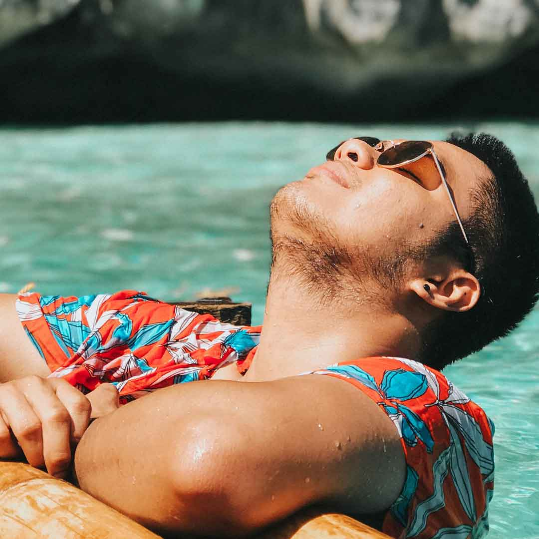 a man wearing a tropical-print shirt leans his face up towards the sun as he relaxes in a pool