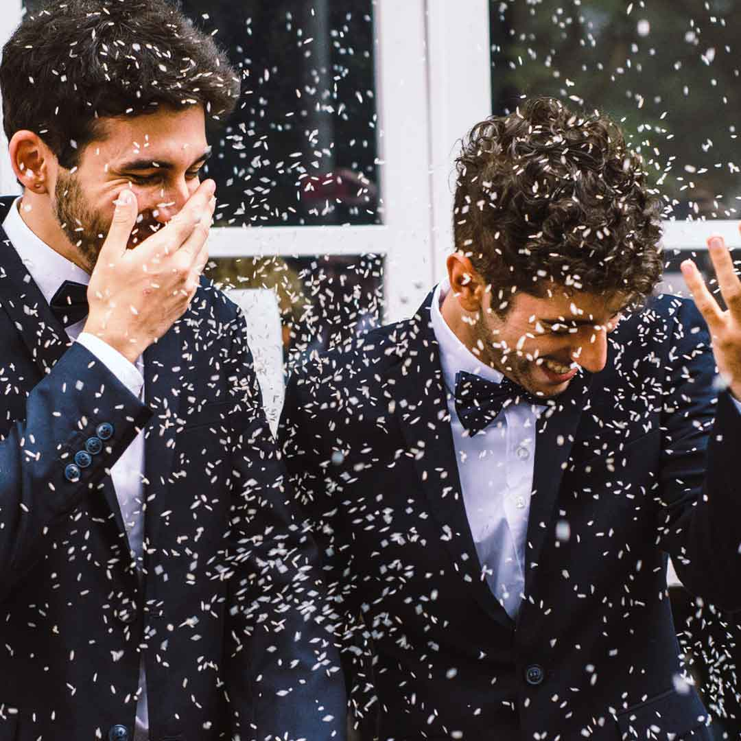 two overjoyed, newlywed men stand hand-in-hand as confetti falls around them